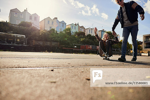 Two friends fooling around  young man pulling young woman along on skateboard  Bristol  UK