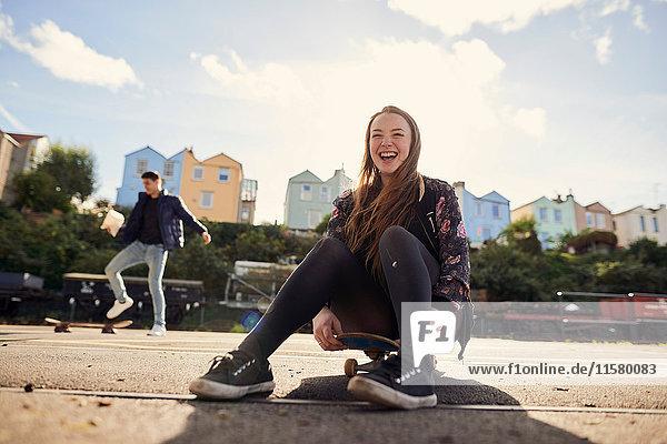 Zwei Freunde albern im Freien herum  junge Frau sitzt auf einem Skateboard und lacht  Bristol  UK
