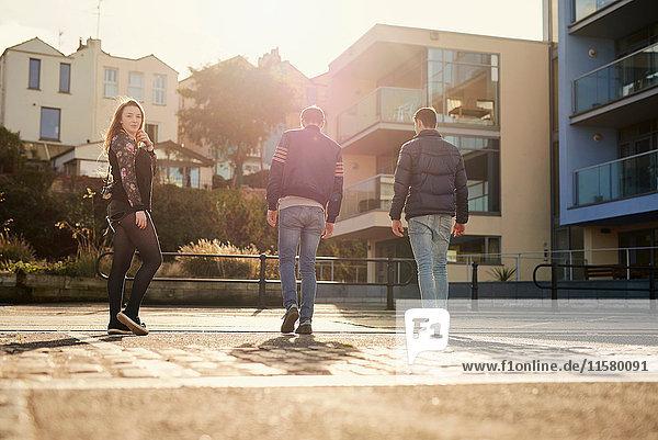 Drei Freunde gehen ins Freie  junge Frau schaut über die Schulter  Bristol  UK