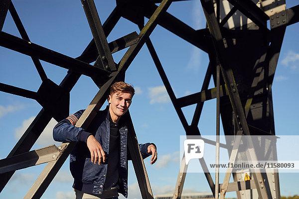 Porträt eines jungen Mannes  Arme um eine Metallstruktur gehängt  Bristol  UK