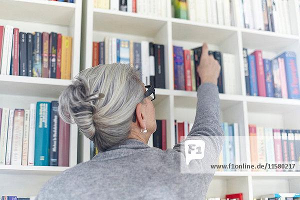 Ältere Frau nimmt Buch aus dem Bücherregal  Rückansicht
