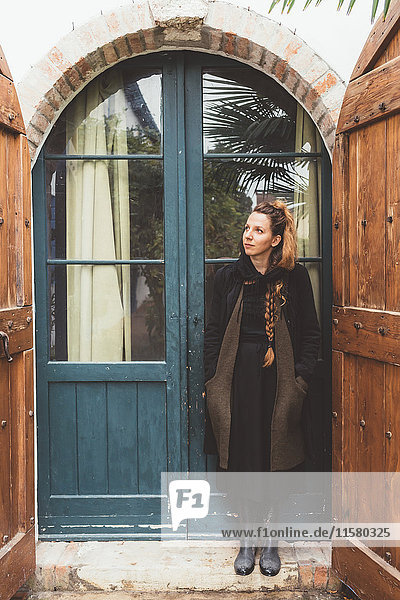 Portrait of young woman looking up from house doorway