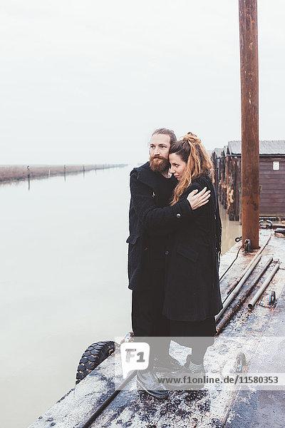 Ehepaar umarmt sich am Ufer des nebligen Kanals