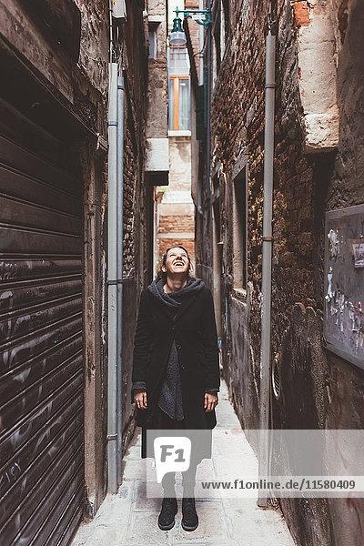 Junge Frau  die aus einer Gasse aufschaut  Venedig  Italien