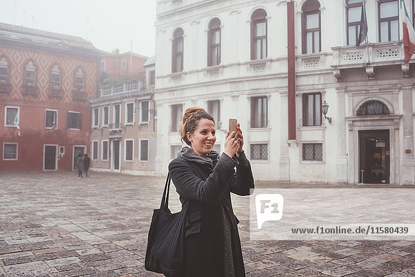 Young woman taking smartphone selfie in misty square  Venice  Italy