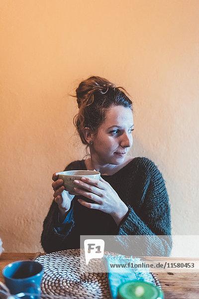 Junge Frau hält Schüssel am Küchentisch