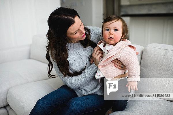 Kleines Mädchen  das aufschaut  während es von seiner Mutter gekuschelt wird