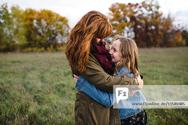 Mother and daughter hugging in meadow  Lakefield  Ontario  Canada