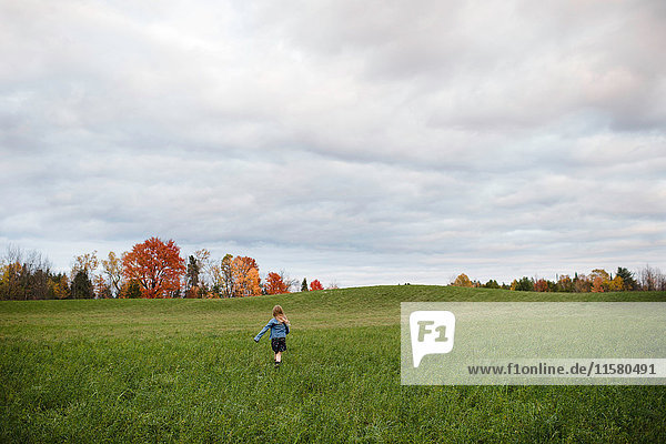Young girl running in open field  Lakefield  Ontario  Canada