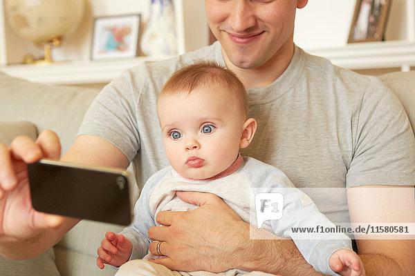 Mittelgroßer erwachsener Mann nimmt Smartphone-Selfie mit Baby-Tochter auf Sofa