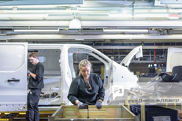 Ingenieurin in Ausbildung am Fließband in einer Autofabrik