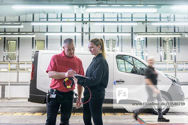 Ingenieurin in Ausbildung mit Mentorin am Fließband in einer Autofabrik