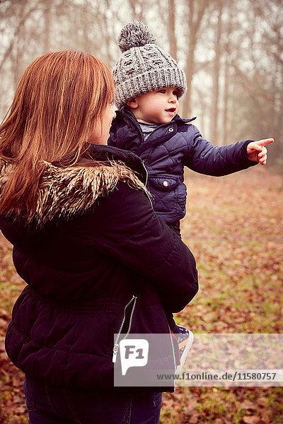 Mittelgroße erwachsene Frau,  die einen Kleinkind-Sohn trägt und in den Herbstwald zeigt