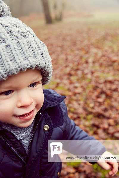 Male toddler in knitted hat in forest