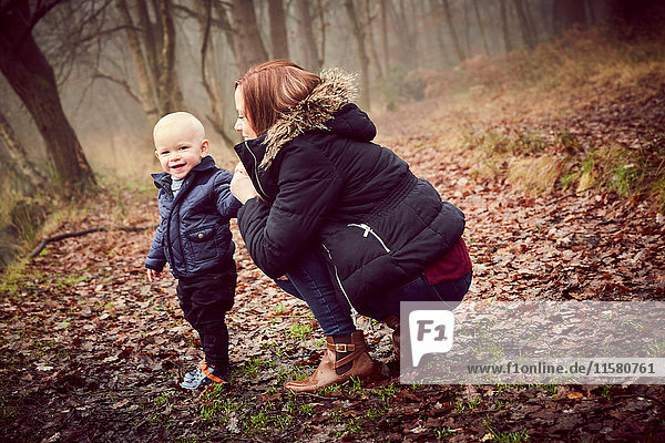 Mid adult woman crouching with toddler son in autumn forest