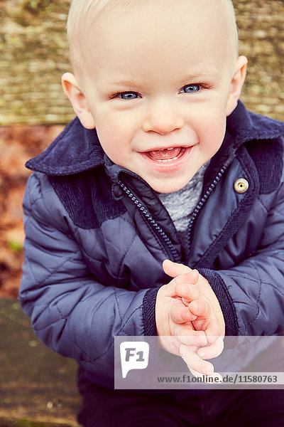 Portrait of blue eyed male toddler on park bench