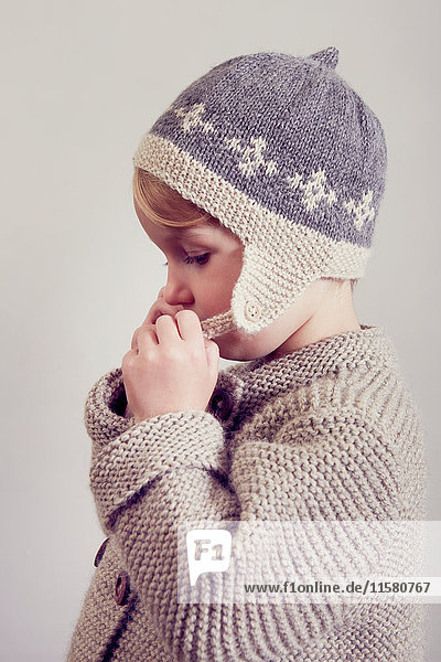 Portrait of girl fastening hand knitted hat