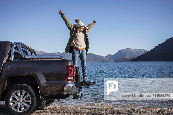 Frau mit offenen Armen auf Pickup am Seeufer in den bayerischen Alpen stehend