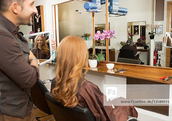 Friseur zeigt Kunden gestylt lange rote Haare im Salon