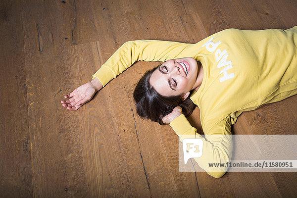 Glückliche junge Frau in gelbem Sweatshirt auf Holzboden liegend