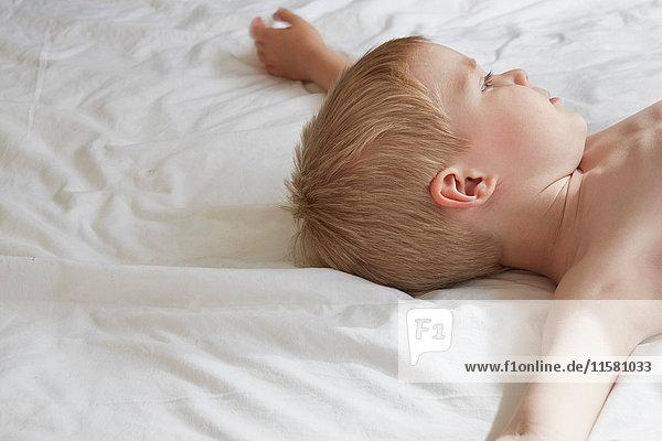 Nacktbrust liegender Junge im Bett und träumen