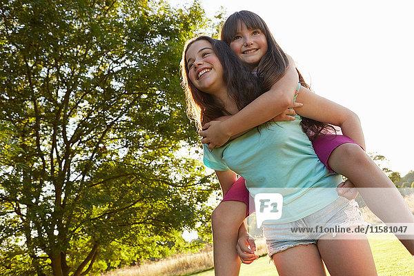 Mädchen gibt ihrer besten Freundin im Park ein Huckepack