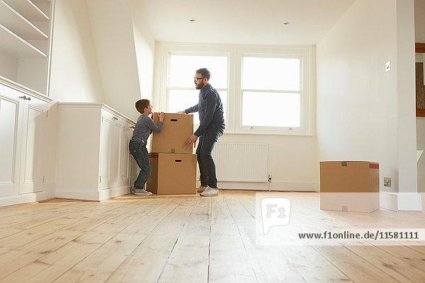 Mittlerer Erwachsener Mann und Sohn stapeln Pappkarton im neuen Zuhause