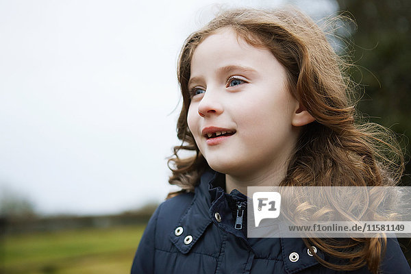 Portrait of girl with long wavy red hair outdoors