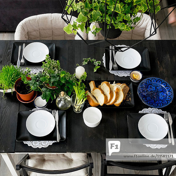 Overhead view of set table with bread slices  fresh herbs and spring onions