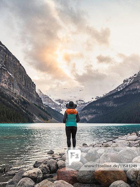 Frau steht am Ufer des Sees  Ansicht von hinten  Rückansicht  Lake Louise  Alberta  Kanada