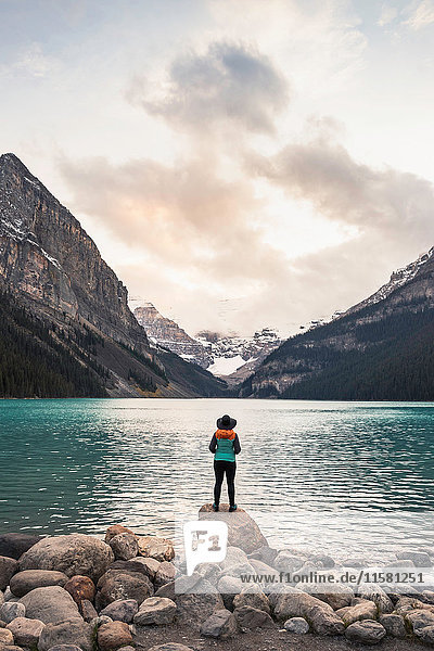 Woman standing on rock  looking at lake view  rear view  Lake Louise  Alberta  Canada