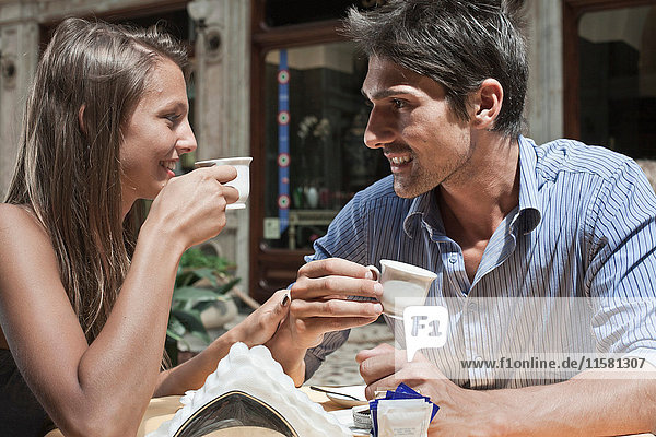Young couple sitting outside cafe  drinking coffee  Turin  Piedmont  Italy