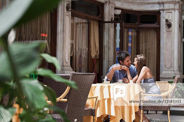 Junges Paar sitzt vor einem Café  Turin  Piemont  Italien