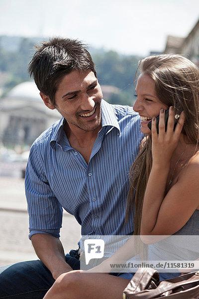 Junges Paar sitzt im Freien  junge Frau benutzt Smartphone  Turin  Piemont  Italien