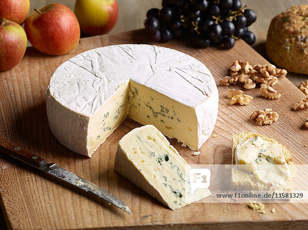 Still life of Blue brie with walnuts  grapes and apples on chopping board