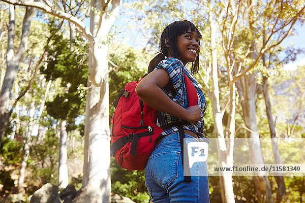 Young woman hiking through forest  looking over shoulder  smiling  Cape Town  South Africa
