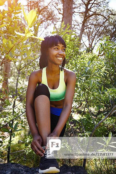 Junge Frau in ländlicher Umgebung  trägt Sportkleidung  bindet Schnürsenkel an Turnschuhen