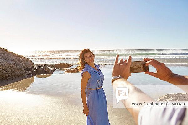 Ein reifer Mann fotografiert eine Frau am Strand  Kapstadt  Südafrika