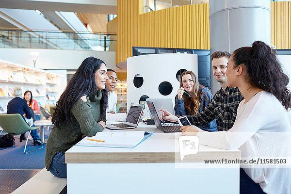 Universitätsstudenten  die Laptops und digitale Tabletts verwenden  arbeiten zusammen