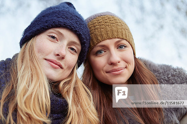 Portrait of two female friends outdoors  wearing knitted hats
