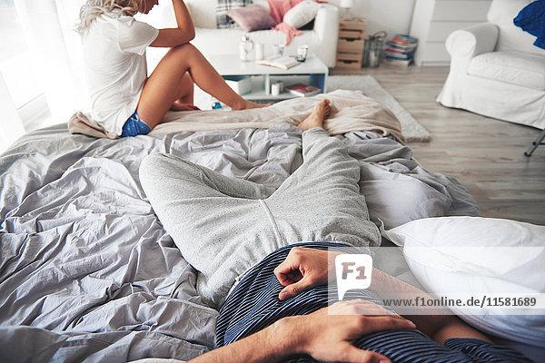 Mann im Bett liegend  Frau am Bettende sitzend