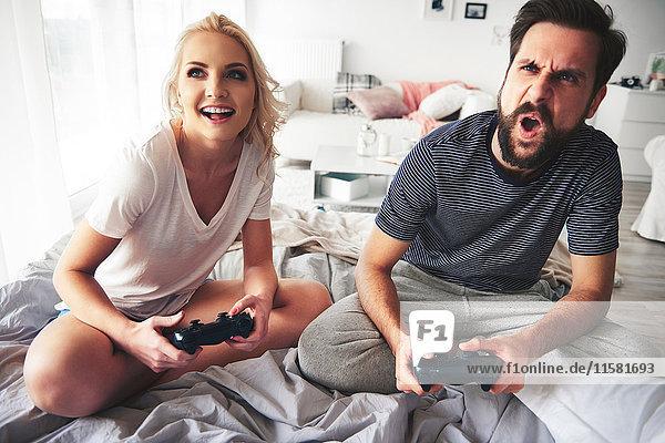 Paar sitzt auf dem Bett  hält Computer-Controller in der Hand  spielt Computerspiel
