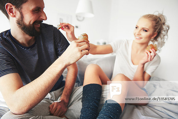 Couple sitting on bed  fooling around  woman sharing pastry with man