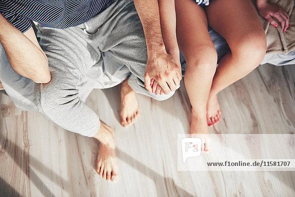 Paar auf der Bettkante sitzend  Hände haltend  Draufsicht