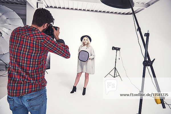 Male photographer photographing female model on studio white background