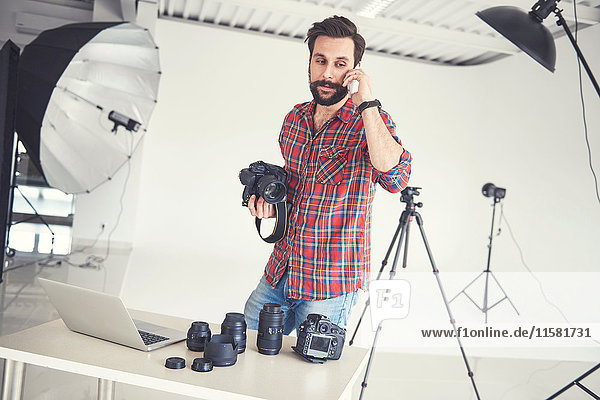 Male photographer making smartphone call in studio photo shoot