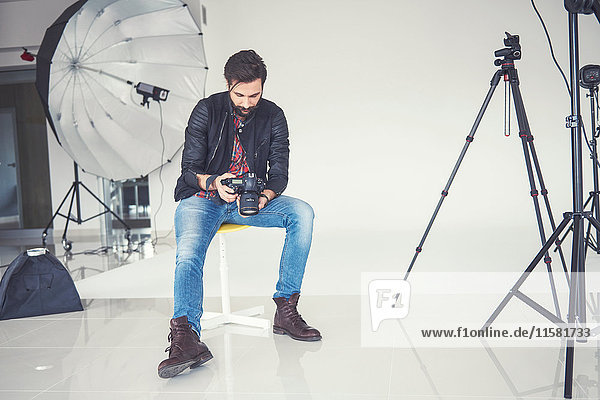 Male photographer reviewing studio photo shoot on digital slr