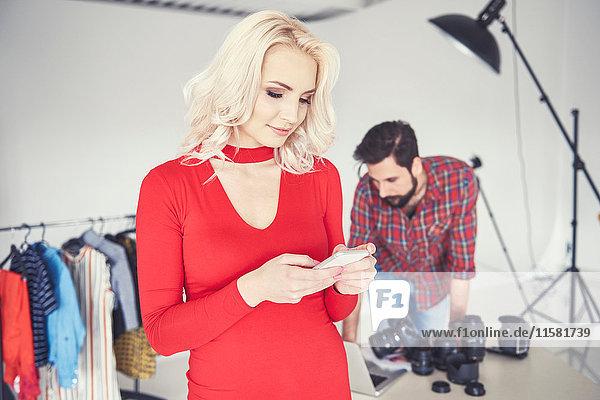 Female model looking at smartphone in studio photo shoot