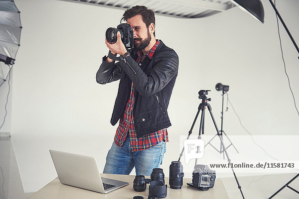 Male photographer testing digital SLR focus for studio photo