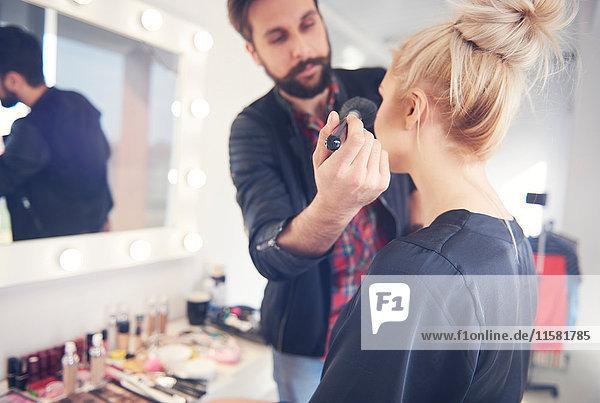 Männlicher Maskenbildner trägt Rouge auf Modell für Fotoshooting auf